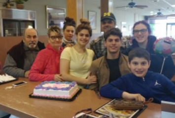 Family smiling at a table, all white with dark hair, of different ages, sheet cake in front of them, one holds a balloon