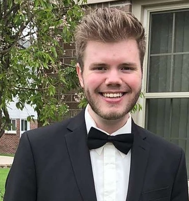Young, blond, white man with facial hair smiles at camera, wears a tuxedo and bowtie