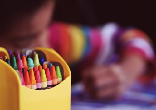 Box of colorful crayons, child drawing blurry in the background