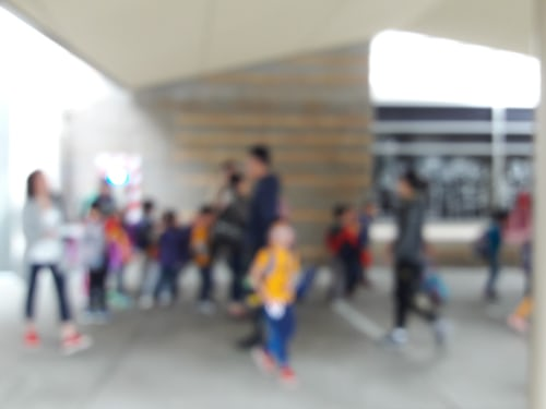 Blurry view of school playground and many children, no figures distinct