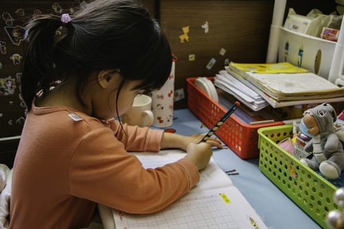 Small child writing in a workbook at table with toys and school supplies