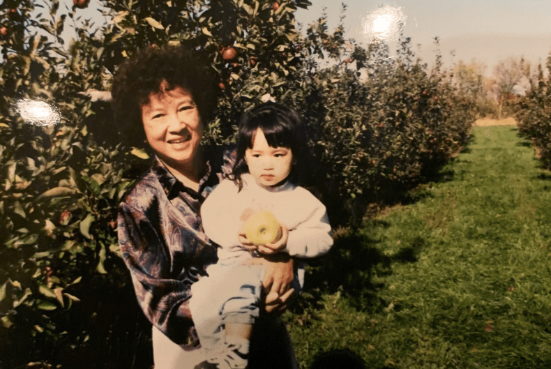 Asian woman smiles and holds young girl holding an apple in an apple orchard, rows of apple trees behind them